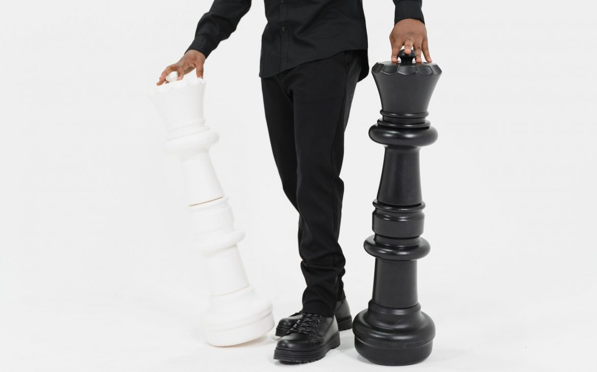a black holding a white and black chess piece